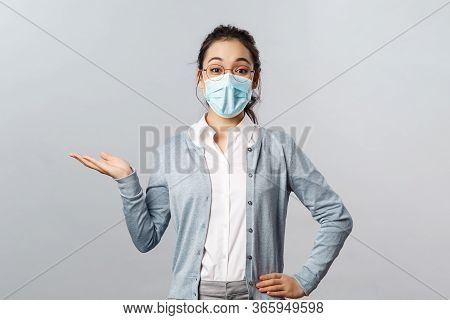 Asian Woman In Glasses And Face Mask Introduce New Company Product Or Banner, Pointing, Holding Prom