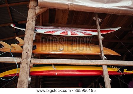 Set Of Different Color Surf Boards In A Stack By Ocean.bali. Surf Boards On Sandy Balangan Beach. On