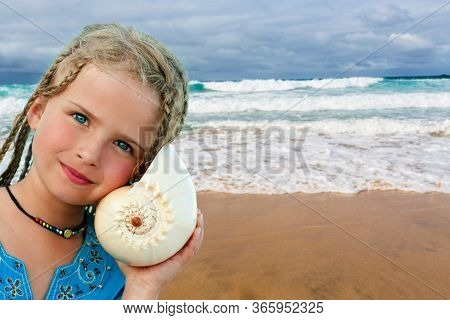 listening to the sea, beautiful young girl with shell on the beach