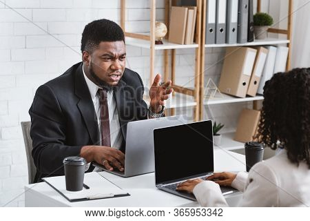 Young African American Coworkers Having Argument At Workplace, Copy Space