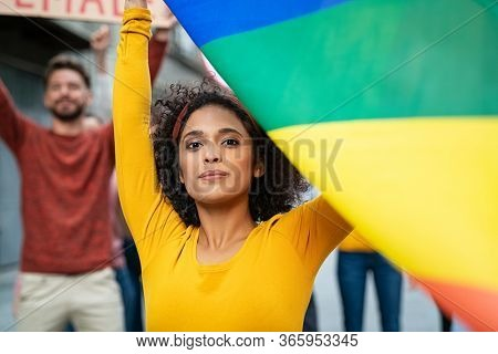 Mixed race young woman at women empowerment strike holding rainbow flag. Proud multiethnic lesbian girl in rally to protest on equality for gay. Girl with group of activists during gay pride parade.