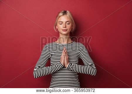 Image of nice young woman in striped sweatshirt meditating with pals together isolated over red background