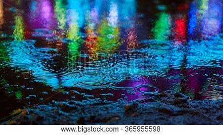 Blue reflections in the water when it rains at night at a fun fair or a fair