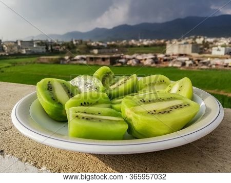 Ripe Peeled Kiwi Fruit Slices In White Plate With Mountains In Background