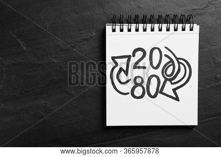 Top View Of Notebook With Numbers 20, 80 And Arrows On Black Slate Background, Space For Text. Paret
