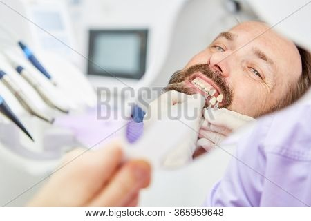 Patient looks in the mirror while adjusting the tooth color in the professional teeth whitening