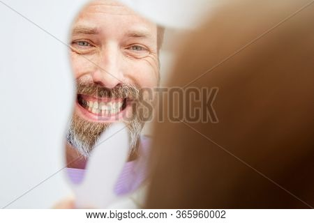 Man at the dentist is happy about his tooth color after professional teeth whitening