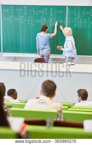 Teacher and student solving math formulas on the blackboard in a university