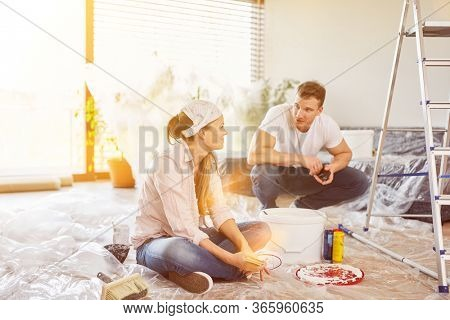 Couple as a home improvement during renovation and paint walls in the home