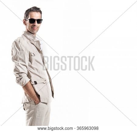 A young man wearing sunglasses and white suit