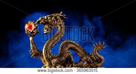 Chinese Dragon Holding A Chrysanthemum Sphere With A Smokey Red Background,  Blue Symbolizing Immort