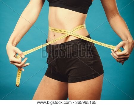 Weight Loss, Slim Body, Healthy Lifestyle Concept. Fit Fitness Girl Measuring Her Waistline With Mea