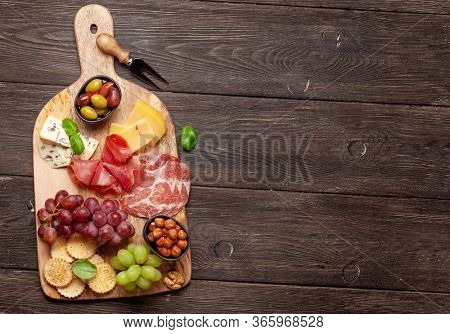 Cheese, meat, grapes and olives antipasto. Appetizer selection on wooden board. Top view with copy space. Flat lay