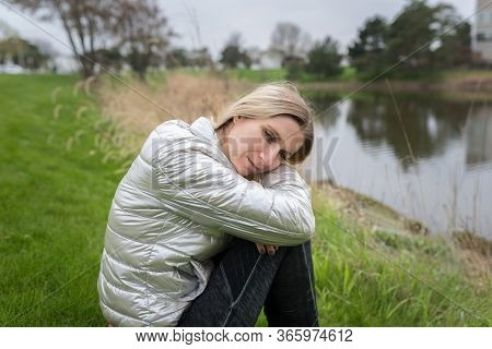 Woman/girl Sitting On A Grass In Front Of Water Of A Lake