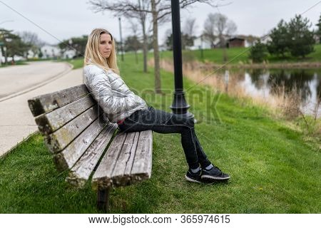 Woman Sitting On A Bench Alone In Front Of Water Of A Lake