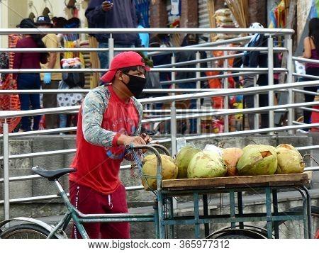 Cuenca, Ecuador - April 23, 2020: Yong Men Wearing Mask Sells Coconuts At The Local Food Market Duri