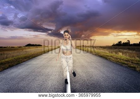 Fit Woman Wearing Sportswear Running Or Jogging Alone On An Isolated Road For Exercise During Social