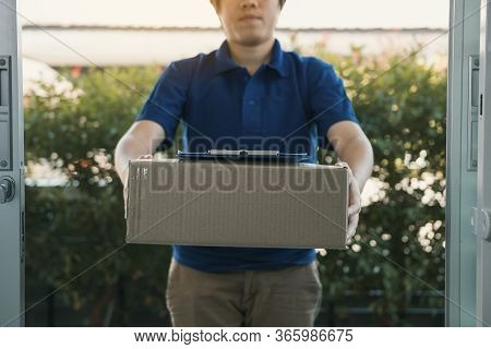 Asian Cargo Carrier Holds A Cardboard Box With The Package Inside And The Recipient Is Signing The P
