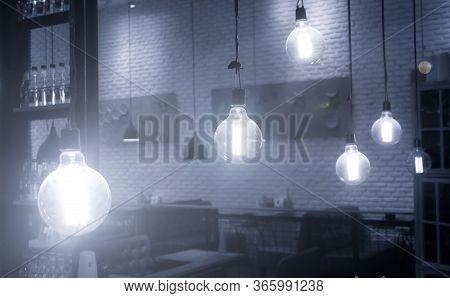 Many Bulbs In The Restaurant, The Light Of The Lamp Illuminates The Restaurant, Dark Background, Man