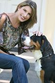 Gorgeous woman with her swiss mountain dog having fun outdoors poster