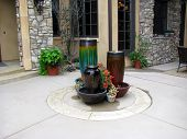 Three large outdoor pot fountains in the center of a front porch entry way poster