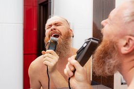 Handsome Cheerful Bearded Man Singing Into Hair Trimmer Instead Of Microphone In Front Of Mirror In