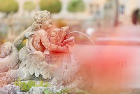 White Statue Of Angel Boy Fountain In Weikersheim, Bavaria, Germany. Europe Travel.