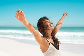 Portrait of healthy young woman standing on the beach with outstretched arms and feeling the breeze. Happy young woman feeling fresh and relaxing at ocean. Latin tanned woman with closed eyes.