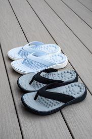 Black And Light Blue Flip Flops On Gray Deck Background