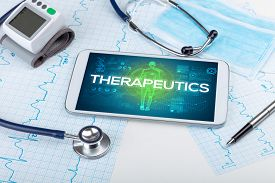 Tablet pc and doctor tools with THERAPEUTICS inscription, coronavirus concept