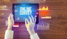 Close-up of hands holding tablet with ONLINE SURVEY inscription, modern business concept