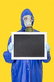 A Man In A Gas Mask Holding An Empty Poster In His Hands. Place For Text. Coronavirus Quarantine Sel