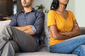 Middle eastern couple sitting back to back after a fight. Young indian couple in fight with arms crossed sitting on couch after quarrel at home. Young mixed race woman and his boyfriend sitting angry.