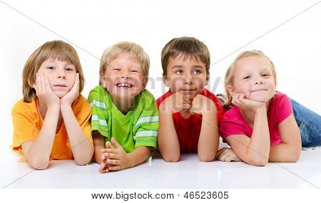 cute children in colored t-shirts lying and smiling, over white background