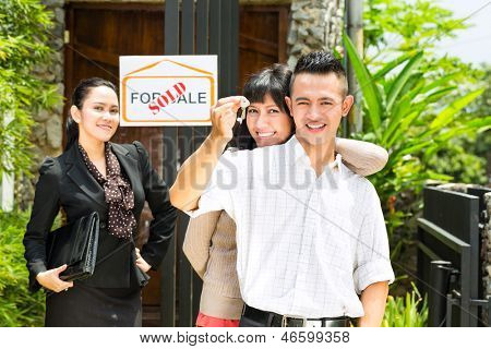 Real estate market - young Indonesian couple looking for real estate apartment or house to rent or buy, the woman holding the keys