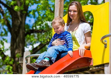 Mother on son playing on a jungle gym