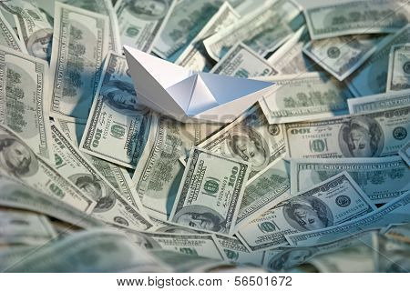 Paper boat at sea of money