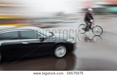 Dangerous city traffic situation with a cyclist and cars in motion blur poster