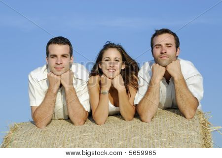 Three young adults on a straw bale