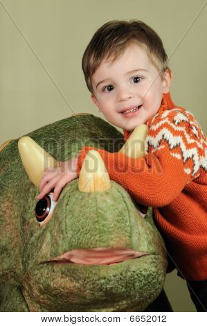 Young boy hugging green dinosaur