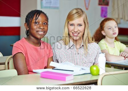 Smiling teacher helping african girl in elementary school class