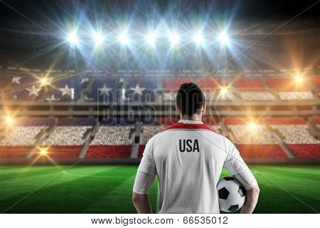 Usa football player holding ball against stadium full of usa football fans
