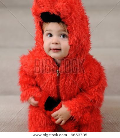 Young boy in fluffy red costume
