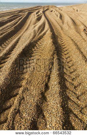 Caterpillar Tracks From Digger On Stony Beach