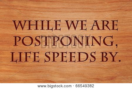 While we are postponing, life speeds by - quote on wooden red oak background