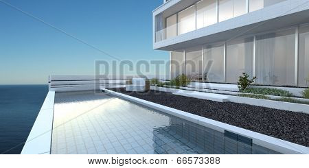 Modern upmarket home with huge glass windows , a patio and swimming pool overlooking the sea against a sunny blue sky
