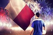 Handsome french football player holding the ball against fireworks exploding over football stadium poster
