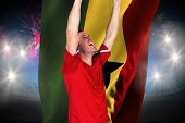 Cheering football fan in red against fireworks exploding over football stadium and ghana flag poster