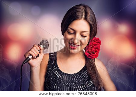 Singer. Portrait of a beautiful young woman with a microphone.