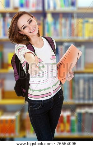 Portrait of happy female college student gesturing thumbsup in library poster